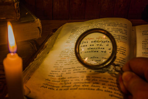 To examine through the magnifying glass the text of the ancient prayer book フォト