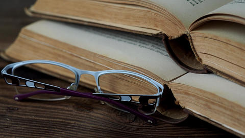 Books and glasses on wooden table Footage