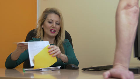 Adult business woman showing documents for client or colleague in office Footage
