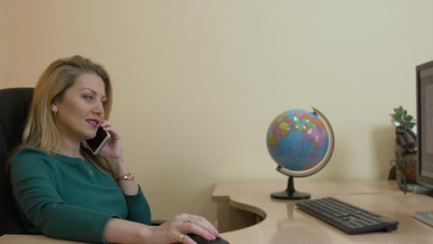 Business woman talking by mobile phone sitting on desk in travel company office Live Action