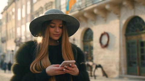 Gorgeous brunette woman in a gray hat standing in the crowded city street and Footage