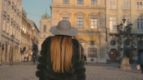Young woman with beautiful blue eyes in a gray hat walking city street with Footage