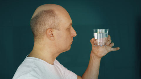 Thirsty mature man drinking water from glass Footage