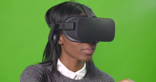 A stationary shot of a lady against a green screen, wearing a VR headset Live Action