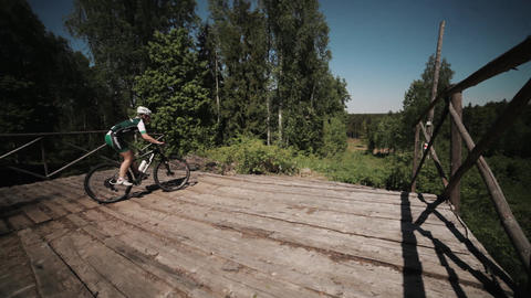 Bicycle freeride race in nature, athlete fast rides upon wooden bridge Footage
