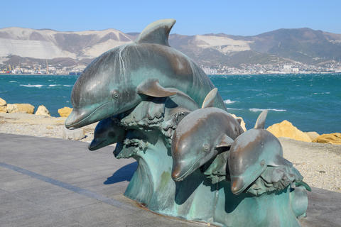 The bronze sculpture of three dolphins on the beach フォト