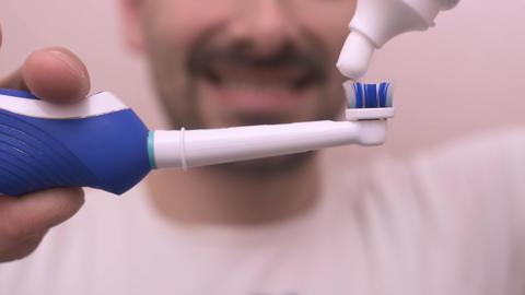 Bearded man starts brushing his teeth in the mirror Footage