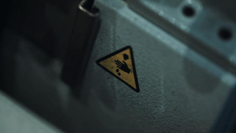 Hazard warning sticker sign, yellow triangle with hand, arrow and two dots Footage