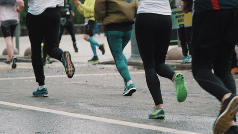 Lots of athletes feet running marathon reflecting in puddle Footage