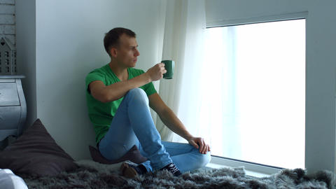 Man drinking coffee and admires view from window Footage