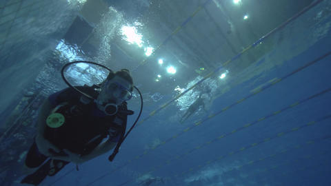 Man scuba diver swimming in deep pool during training on diving course Footage