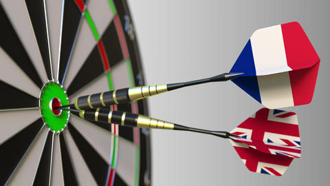 Flags of France and the United Kingdom on darts hitting bullseye of the target Footage