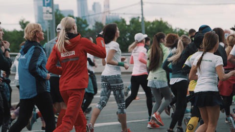 Healthy people running marathon on city river embankment Live Action