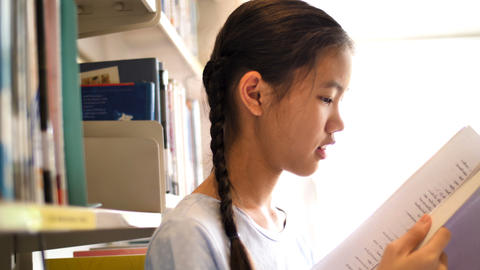 4K Asian teenager student reading a book in school library for inspiration,Shoot Archivo