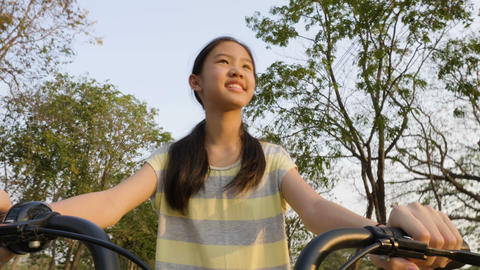 Slow motion 4K of Happy Asian preteen girl enjoying to ride bicycle in the park 영상물