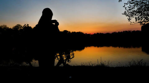 Slow motion 4K Silhouette of Girl take a photo with smartphone near the lake at Archivo
