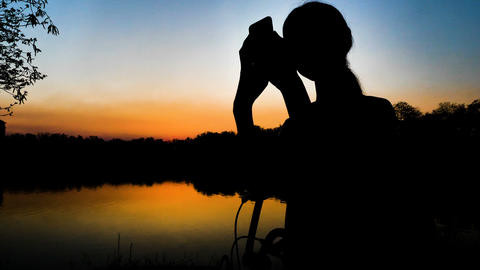 Slow motion 4K Silhouette of Girl take a photo with smartphone near the lake at Footage