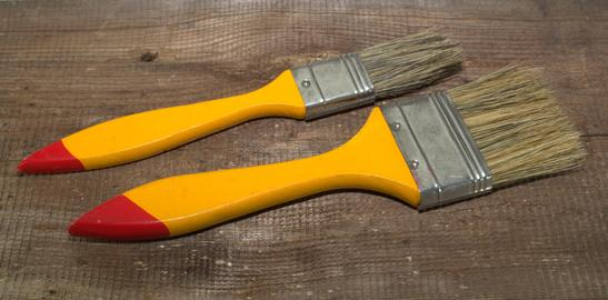 Two paint brushes 1 inch wide and 2 inches wide with yellow handles on a wooden Photo