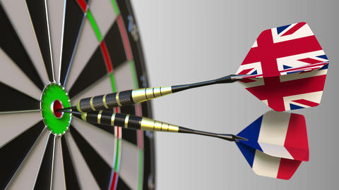 Flags of the United Kingdom and France on darts hitting bullseye of the target Footage