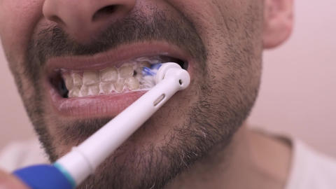 Bearded man brushing his teeth in the mirror open mouth Footage
