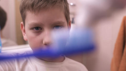 Young boy squeezes toothpaste on toothbrush and brushes teeth Footage