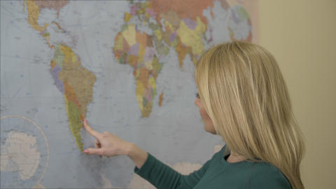 Beautiful woman touching finger world map on wall and dreaming about traveling Footage