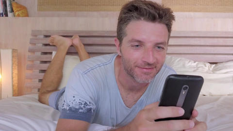 man with blue eyes in bed using internet social media app on mobile phone Archivo