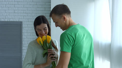 Excited woman surprised by bunch of flowers from man Footage