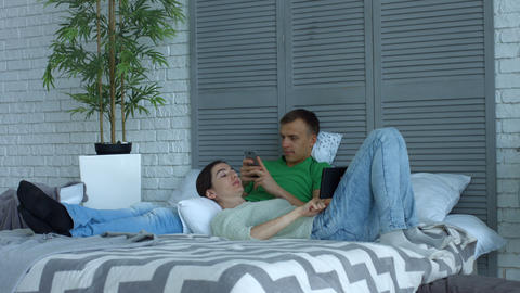 Loving couple with digital devices relaxing on bed Footage