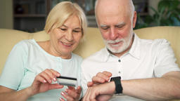 Cheerful good-looking senior couple sitting on sofa. Buying online with credit Footage