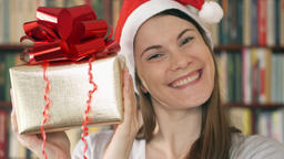 Woman in Santa's hat with present. Female with golden gift box with red ribbon Footage