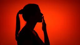 Silhouette of woman making gesture blowing air kiss on red background. Concept Footage