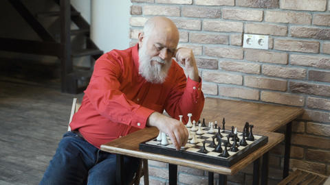 Lonely mature man play chess with himself Footage