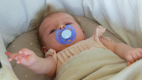 Three month baby lying on a blanket with a pacifier. The baby's face close up Footage