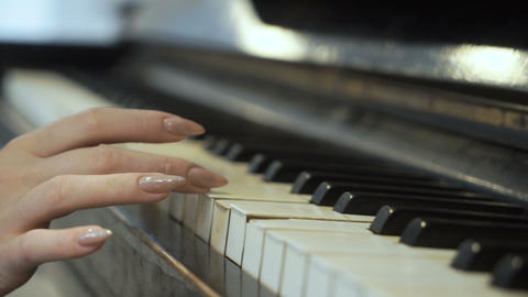 Woman gently touches piano keys Footage