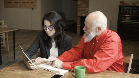 Young woman with mature man looks on screen of digital tablet and talks about it Footage