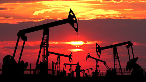 Field of oil pumpjacks against red dusk Footage