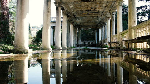 Slow motion stone falls into a puddle in an old beautiful building with columns ビデオ