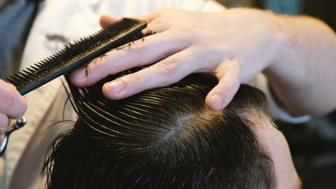 Hairdresser cuts hair to man in barbershop close-up Footage