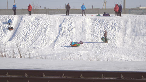 People stand on the hill and watch as children are sledding Footage
