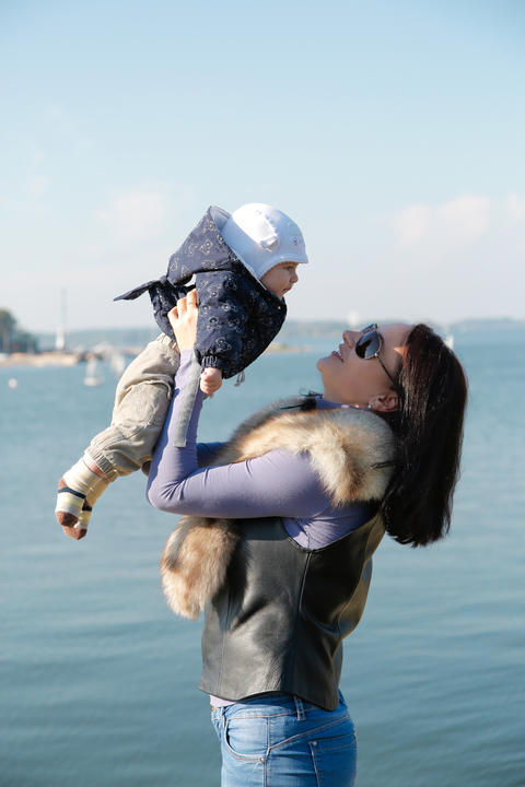 Mom and son have fun on the shore of the blue sea Photo