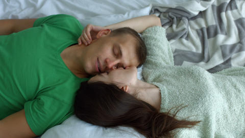 Romantic couple lying on the bed face to face Footage