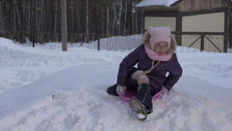 Portrait girl riding on snow hill during winter vacation. Christmas vacation Live Action