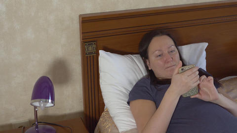 Relaxing woman lying on bed and reading message on email in mobile phone. Text Footage