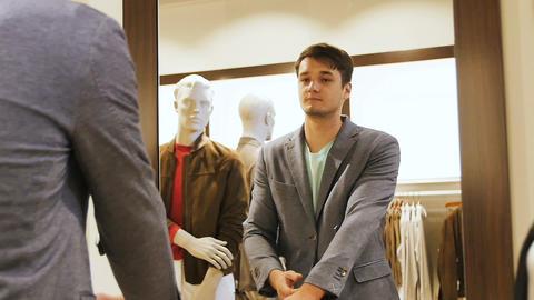 Man Tries on Grey Jacket Looks in Mirror in Mall Archivo