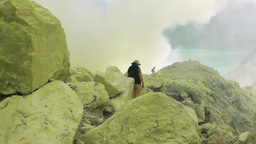 Tourists are among the blocks of sulfur at the bottom of the crater of Ijen volc Footage