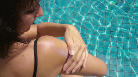 Woman Applying Sun Cream At The Swimming Pool stock footage