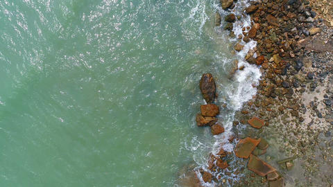 Low aerial shot flying over sea waves crashing on rock Footage