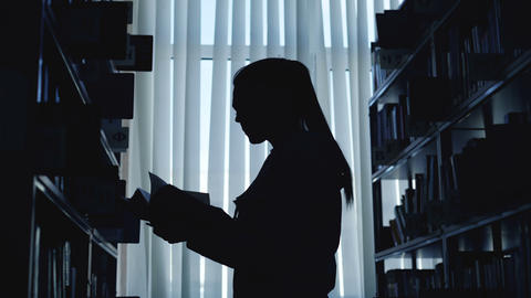 Silhouette of young student girl standing among bookshelves in big library Footage