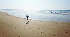 Aerial Drone View Of Sportive Woman Running On Beach Archivo
